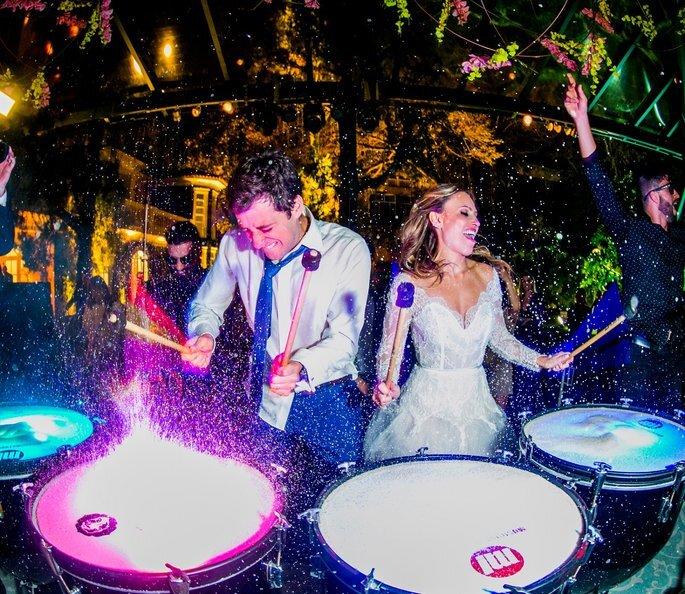 Casal de noivos tocando percurssão na pista de dança