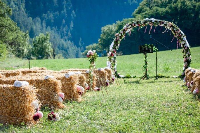 Arche en fleurs et bottes de foin où s'asseoir pour un mariage champêtre