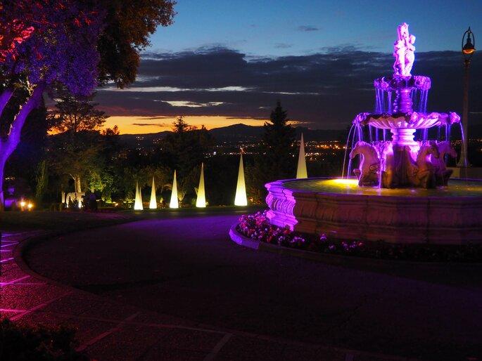 Extérieurs d'un lieu de réception de mariage illuminés, fontaine éclairée et lampadaires originaux