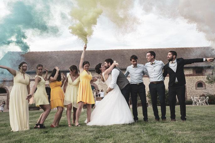 Caprice d'objectif - Photographe de Mariage - Val d'Oise - Photographie où posent des mariés qui s'embrassent et leurs proches qui rient et s'amusent, des fumigènes à la main