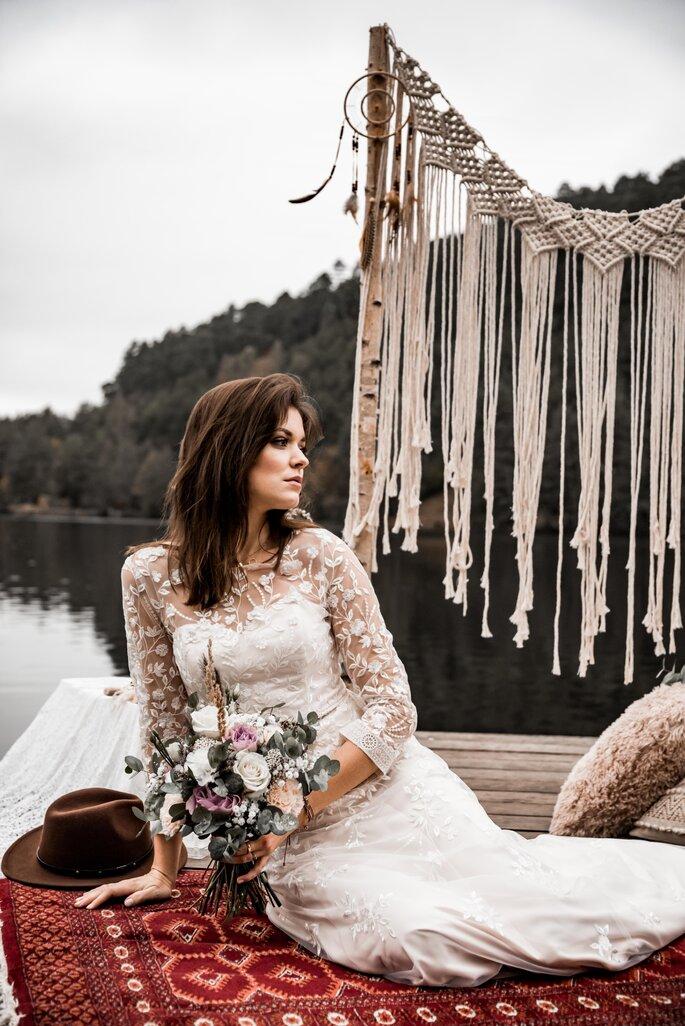 Eine Braut sitzt auf einem Bootssteg und hält einen Brautstrauß in der Hand.