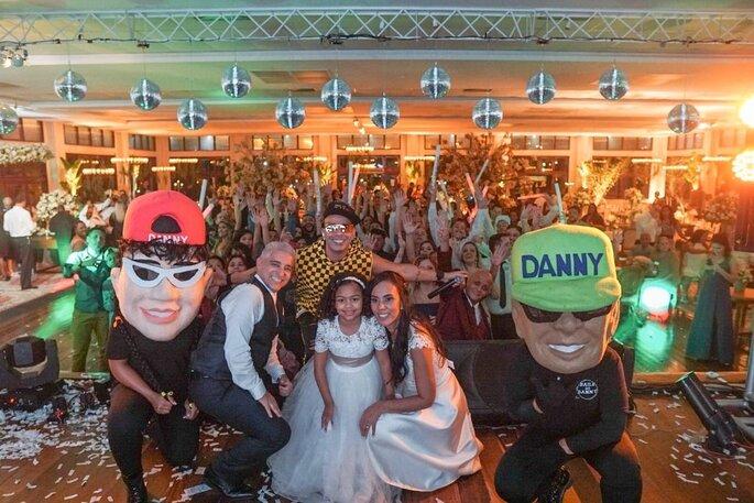 Noivos posam om o cantor no palco da festa