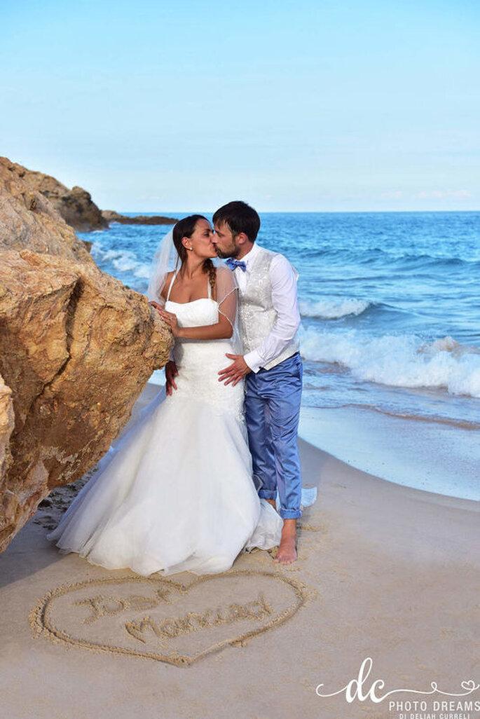 Ein Brautpaar steht barfuß an einem Felsen am Strand und küsst sich.