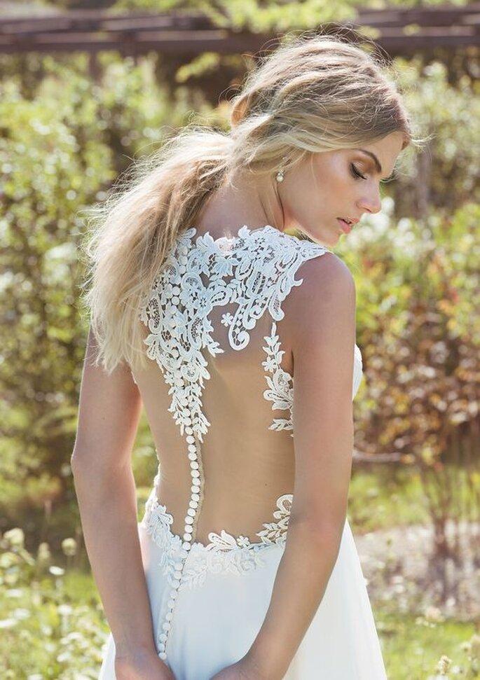 Eine Braut steht in einem Garten und zeigt den verführerischen Rückenausschnitt ihres Brautkleides.