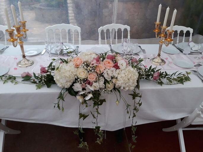 La table des mariés est décorée avec des roses de couleurs pastels et des chandeliers dorés