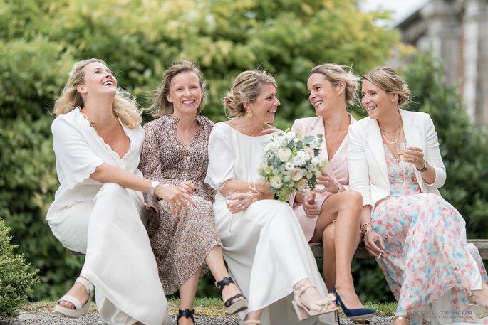 La mariée est assise sur un banc avec des femmes de son entourage, elles rient