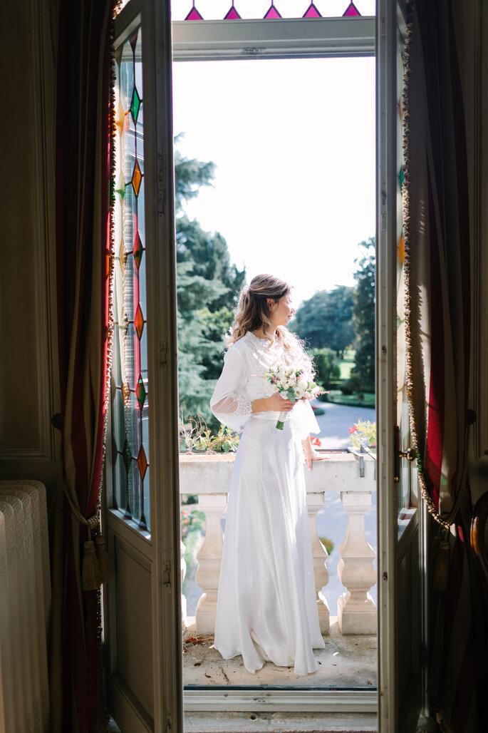 sposa in bianco con bouquet alla finestra