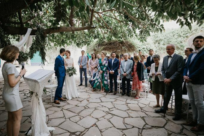 Les invités debout pendant que l'officiante de cérémonie laïque unit les mariés
