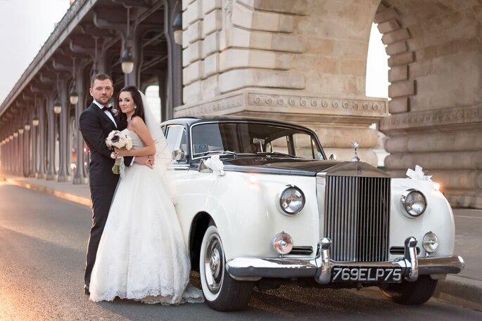 Un couple de mariés devant une Rolls Royce 1960.