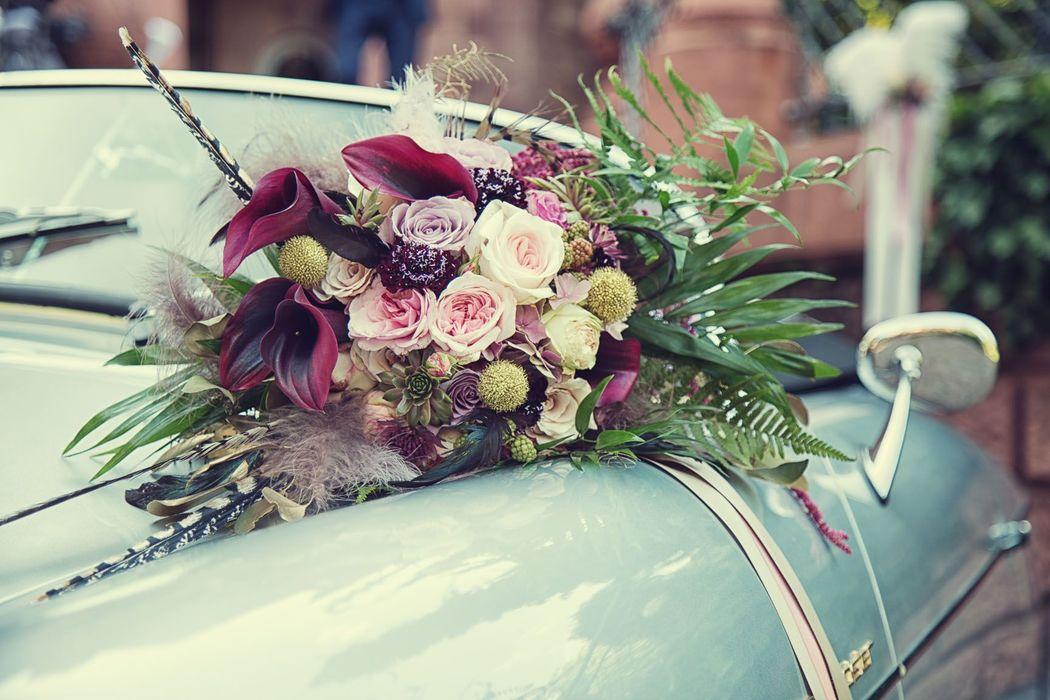 Angesagter leicht abfallender Brautstrauß im Vintage Stil mit verschiedenen Federn und viel grünem Beiwerk Foto: Simon Skroban Fotografie