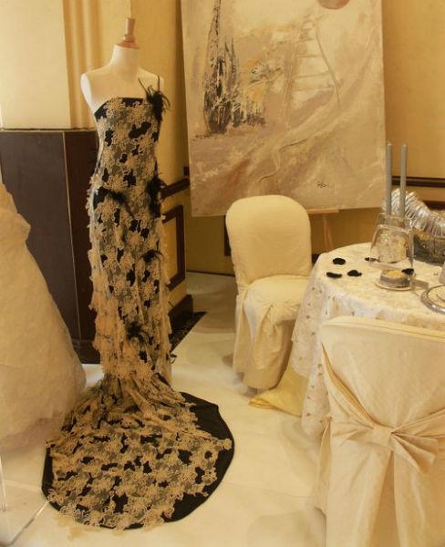 Robe corset en satin de soie noir, dentelle appliquée, découpée pour créer des assymétries et du relief. Plumes noires et strass.