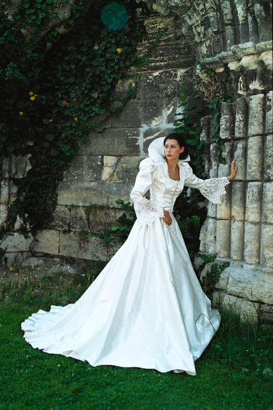 L'AUBE   Cette création de mariage est composée d'une veste bustier en mikado de soie blanche lacée sur le devant, agrémentée de dentelle vénitienne, et rehaussée d'un col « Médicis »…   La jupe à crinoline laisse naître une traîne… Création Léa Madeleine couture.