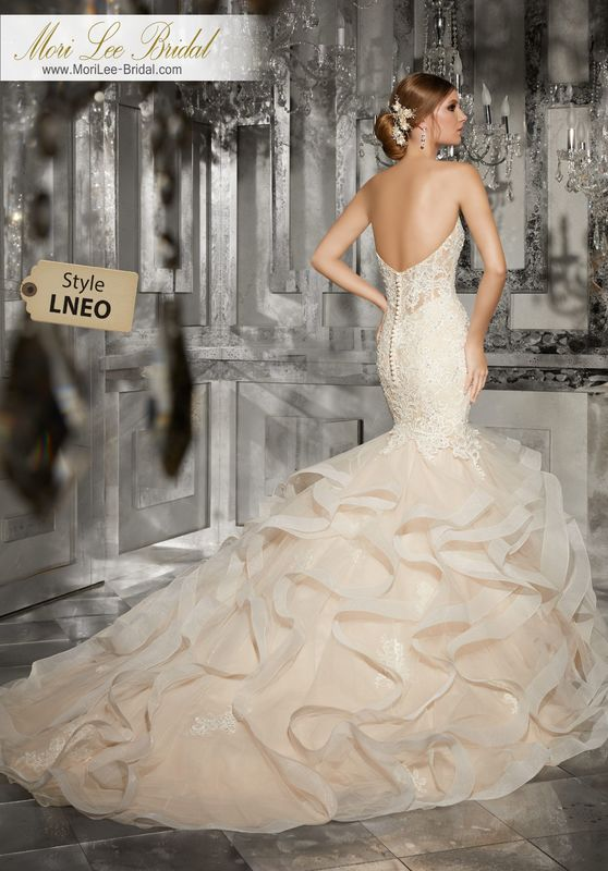 Style LNEO Marguerit Wedding Dress  Intricate Re-Embroidered Lace Appliqués and Crystal Beading Adorn the Sweetheart Bodice on this Breathtaking Wedding Dress. A Flounced Tulle Mermaid finished with Horsehair Trim Completes the Look. Available in Three Lengths: 55″, 58″, 61″. Colors Available:Ivory, White, Ivory/Light Gold