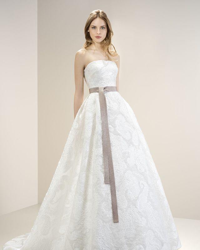 Роскошное платье из белой порчи А-силуэта со шлейфом. Талию подчеркивает изысканная лента лилового оттенка.