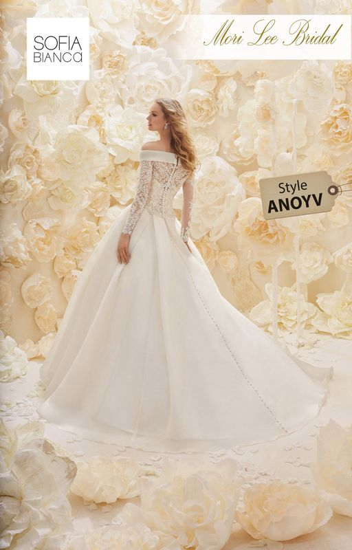 A TEXTURED ORGANZA GOWN WITH A RUCHED STRAPLESS BODICE AND OVERSIZED PLEATED SKIRT WITH A REMOVABLE OFF THE SHOULDER BUTTON BACK LACE JACKET  COLOURS IVORY