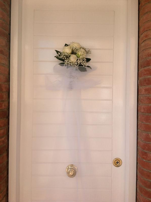 Detall porta de casa la núvia. Pom amb roses blanques i nubolosa. Llaçada de tul blanc fins al terra.