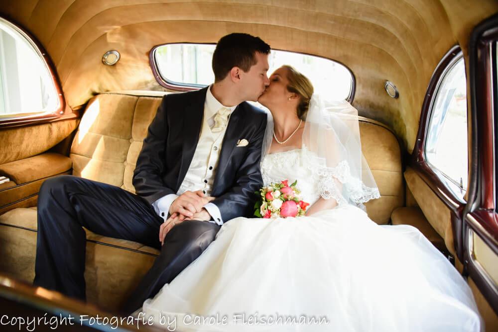 Beispiel:Und bevors los geht noch ein frisch vermählter Kuss im Oldtimer Auto,Foto:Carole Fleischmann Fotografie