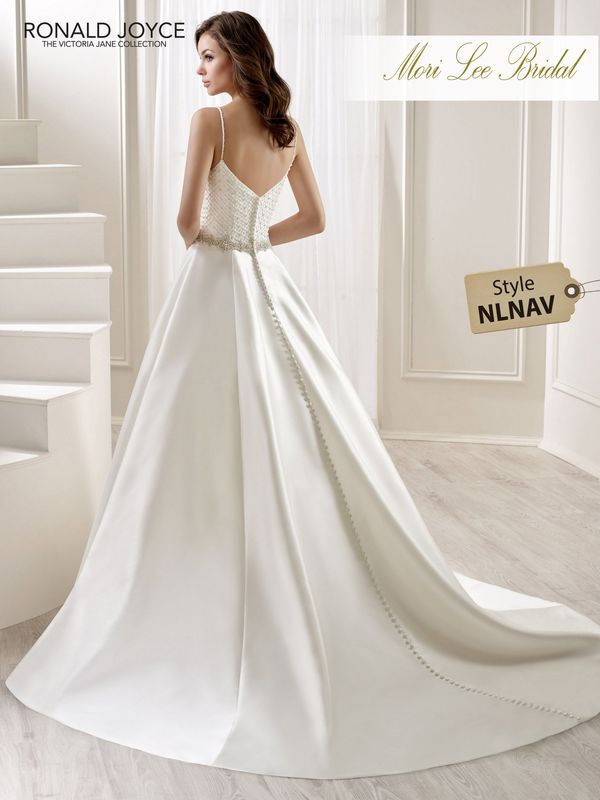 Style NLNAV LEXEY A SPECIAL SATIN A-LINE DRESS WITH A UNIQUE BEADED TULLE BODICE, THIN SHOULDER STRAPS, BUTTON BACK DETAIL AND A BEADED WAISTBAND. PICTURED IN IVORY.  COLOURS IVORY