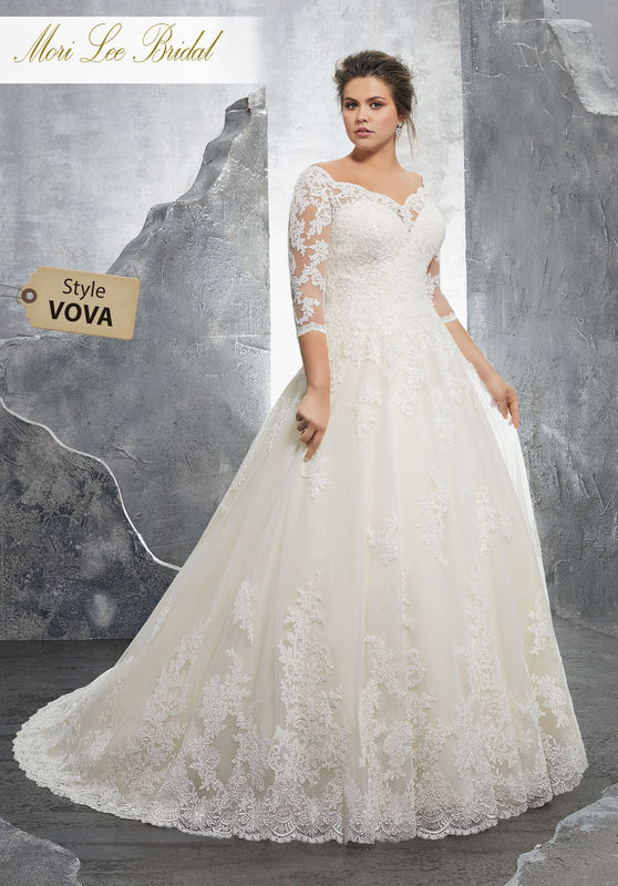 Style VOVA Kosette Wedding Dress  Classic Tulle Bridal Ball Gown with Frosted Alençon Lace Appliqués on and 3/4 Sleeves. A Zipper Back Closure Trimmed in Covered Buttons Completes the Look. Available in Three Lengths: 55″, 58″, 61″. Colors Available: White, Ivory, Ivory/Champagne