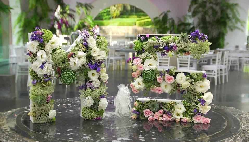 Detalle floral en la fuente con las iniciales de los novios