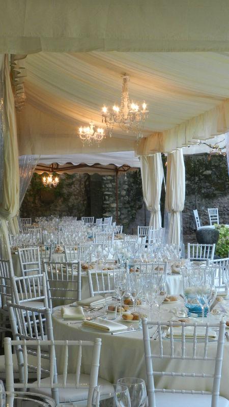 lampadario bianco, tavoli tondi con chiavarine bianche
