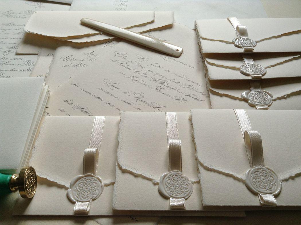 Il Calligrafo - Inviti in carta Amalfi formato unico autochiudibile avorio rosato e formato A4 avorio per Wedding program. Manoscritti in nero ferrogallico con sigillo e nastro raso in tinta.