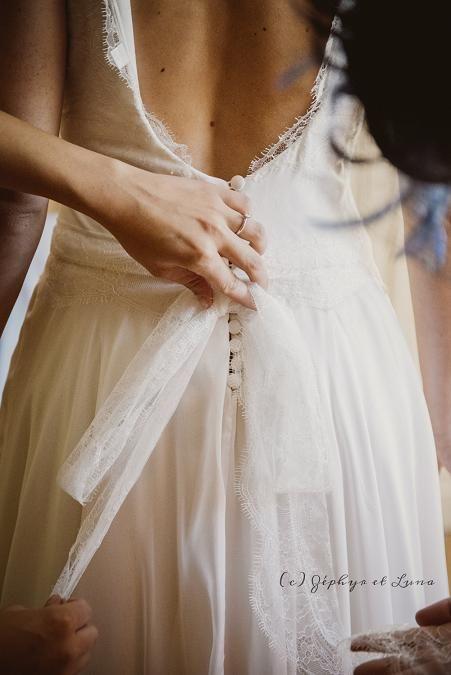 Inès, détail : habillage le jour J....mise en place du noeud en dentelle et du double face transparent pour coller la dentelle le long du dos.