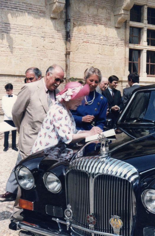 La Reine Elisabeth d'Angleterre à Caumont, signant le livre d'or sur le capot de sa Rolls.