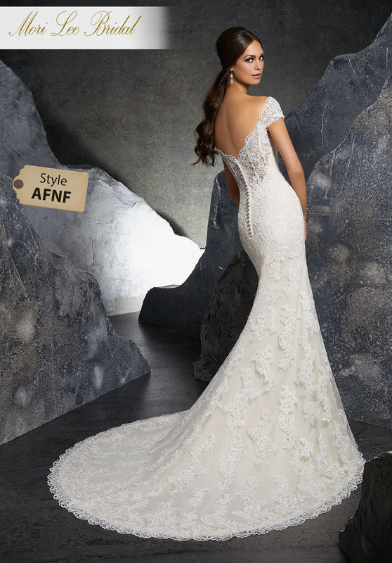 Style AFNF Kinley Wedding Dress  Classic Fit and Flare Wedding Gown Featuring Frosted Alençon Lace Appliqués on Net. A Romantic Off-the-Shoulder Neckline and Wide Scalloped Hemline Complete the Look. Available in Three Lengths: 55″, 58″, 61″. Colors Available: White, Ivory, Ivory/Champagne