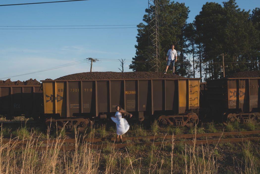 noivo em cima do trilho do trem e noiva na parte de baixo dançando