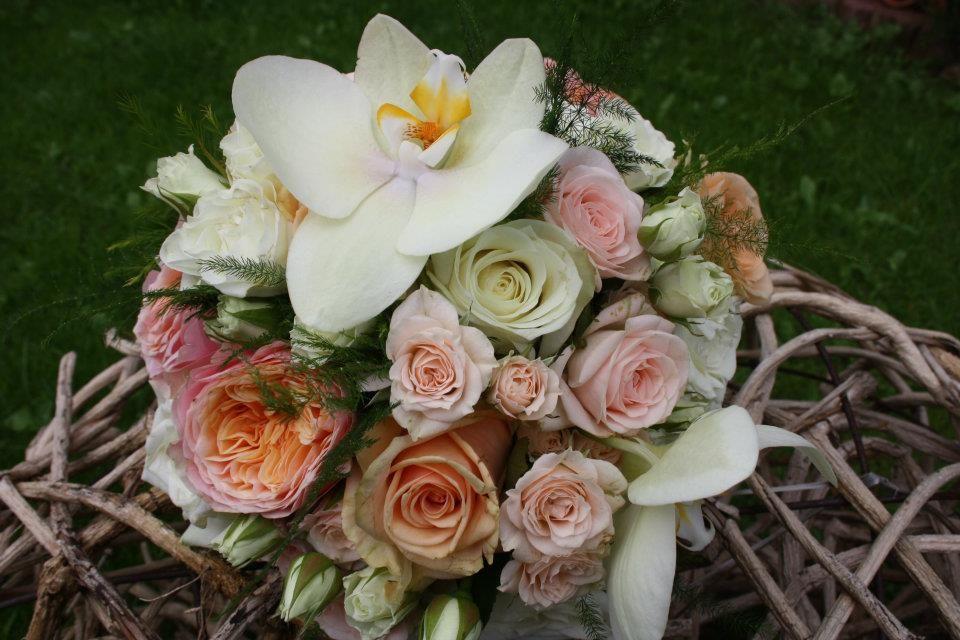 Eine Orchidee als Krönung der zarten Rosen in rosé und apricot.