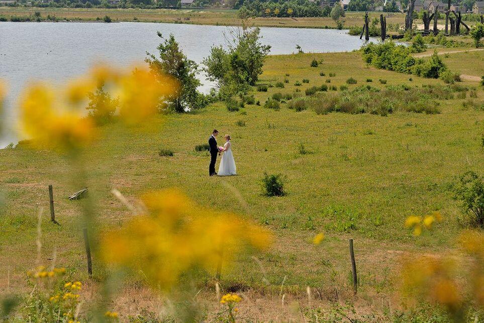 Deze bruid wilde graag een paar foto's met wat meer omgeving erop. hier stonden net gele bloemen te bloeien, dus die staan prachtig onscherp op de voorgrond.