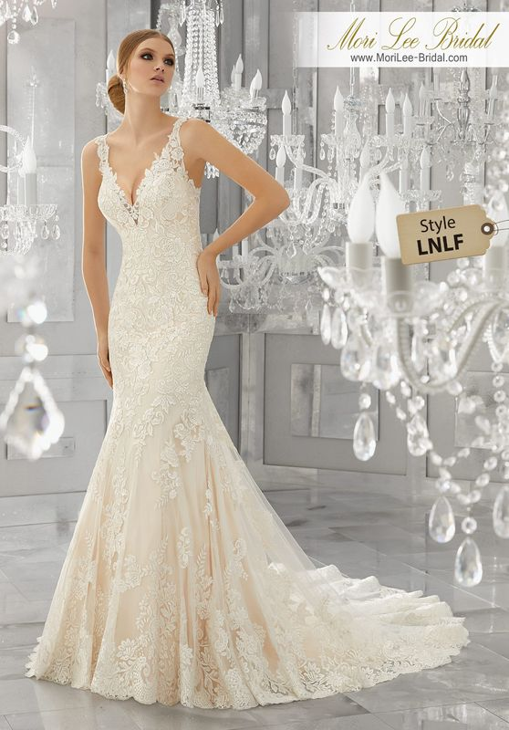 Style LNLF Madora Wedding Dress  Frosted, Embroidered Lace Appliqués Accent the Bodice and Wide Scalloped Hemline on This Fit and Flare Wedding Dress. A Deep V-Neckline and Removable Diamanté Beaded Organza Belt Complete the Look. Belt also Sold Separately as Style NXOFI. Available Available in Three Lengths: 55″, 58″, 61″. Colors Available: White, Ivory, Ivory/Light Gold.